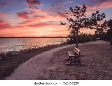 A public bench in a park next to a lake makes a peacefull place for meditation