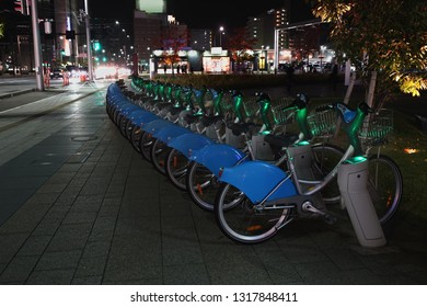 Public bicycle service that is parked on the road at night.