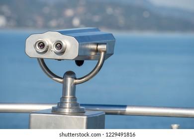 Public binocular on sea shore, close up. Coin operated binocular viewer on blurred background of sunset and sea. Batumi, Georgia