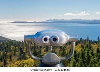 Public binoculars in front of a view over the Forillon National Park, Gaspe Peninsula, Quebec, Canada (montage)