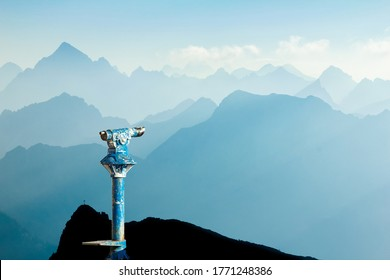 Public binoculars provide far view to distant blue mountain ranges silhouette in early Morning Sunlight. Foresight and vision for new and creative business concept and ideas. Alps, Allgau Bavaria Ge
