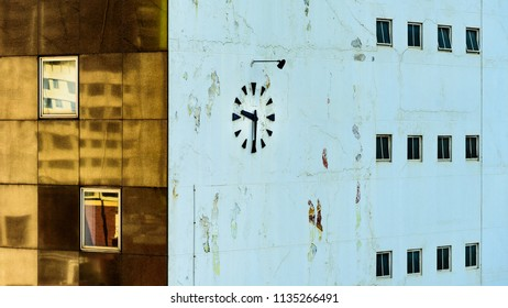 A public clock on the decaying side of a city buliding