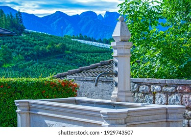 Public drinking potable water fountain in italian village in the Alps mountains, rural landscape, Italy