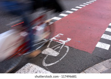 Public facilities for sustainable transportation. Commuter passing by on bicycle on an urban lane. Motion blur. Framed copyspace on red lane.