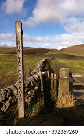 A public footpath marker post along fields up the side of a hill in the Peak District, Derbyshire England UK. There is a small wooden pedestrian gate behind the post next to a five bar livestock gate.