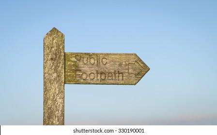 A Public footpath sign set against a light blue sky