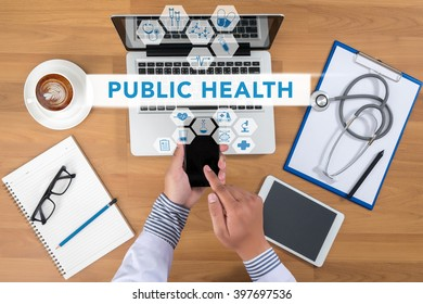 PUBLIC HEALTH CONCEPT   Doctor working at office desk and using a mobile touch screen phone, computer and medical equipment all around, top view, coffee