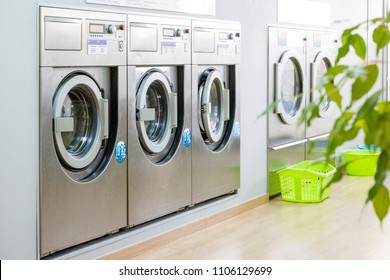 Public laundry with modern, silver washing machines in a row