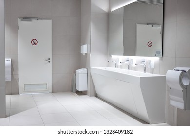 Public lavatory in shopping mall consisiting of ceramic basin, hand dryer and door with sign that smoking is forbidden. Modern clean ladies restroom or toilet for passengers in airport terminal