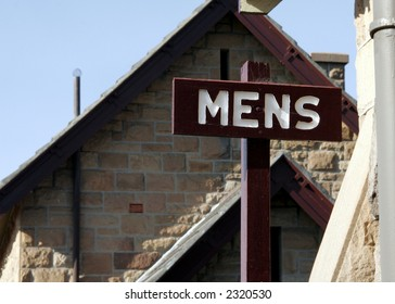 Public Mens Restroom / Toilet Sign On Wood In Front Of A Brick House