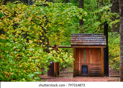 A public outhouse sits alongside the McKenzie Pass scenic highway amongst autumn turning leaves on trees and shrubs.