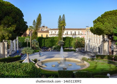 Public park called Bellini Garden (Giardino Bellini) in the city of Catania, Sicily,  historic buildings on the sides, a fountain basin in the middle, mediterranean trees and plants all around, summer