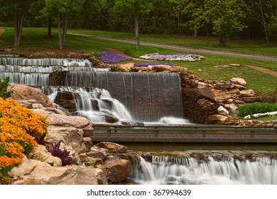 A public park with cascading water and beautiful flower beds
