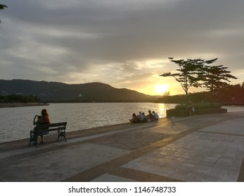 A public park during sunset people are waiting to see beautiful view of sun goes with enjoyment. Recreation place with Trails for walking biking adjacent to bodies of lake water, bench for sitting.