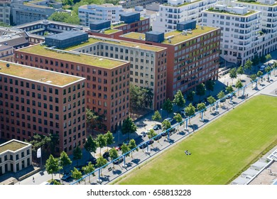 Public park with people and corporate buildings from above - city aerial of Berlin
