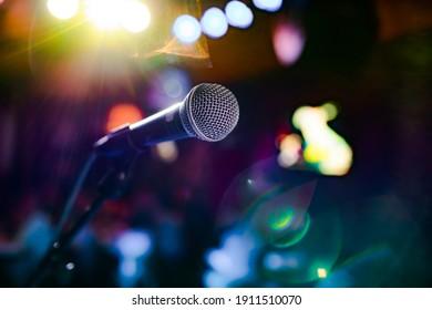 Representación pública en el escenario Micrófono en el escenario contra un fondo de auditorio. Profundidad superficial del campo. Representación pública en el escenario.
