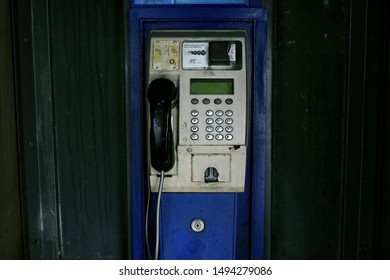Public phone booth with metal button phone inside and blue box around it