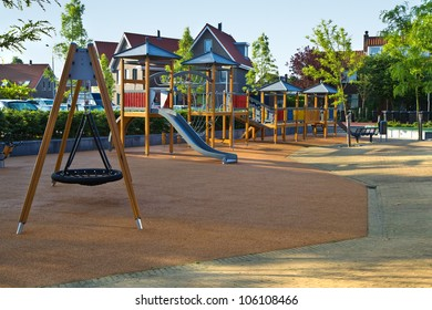 Public playground with colorful wooden climbing construction, swing, slides and rubber floor for safe playing