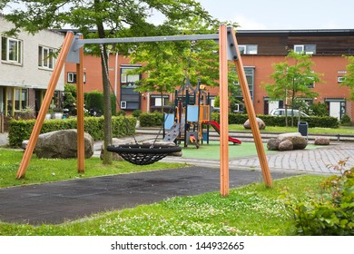Public playground in modern suburb with colorful wooden climbing construction, swing, slides and rubber floor for safe playing