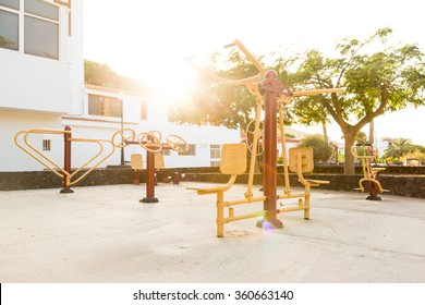 A public playground in a small town of Spain with outdoor fitness machines at sunset