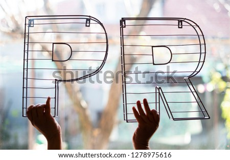 Public Relations letters in front of the window. Hands hold 3D metal letters on backlight. Marketing and business conception.