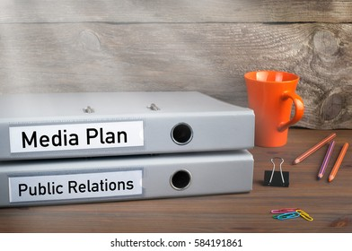 Public Relations and Media Plan - two folders on wooden office desk
