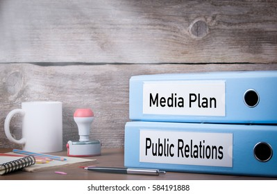 Public Relations and Media Plan. Two binders on desk in the office. Business background