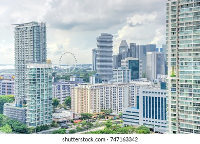 Public residential condominium building complex and downtown skylines at Kallang neighborhood in Singapore. Storm cloud sky.