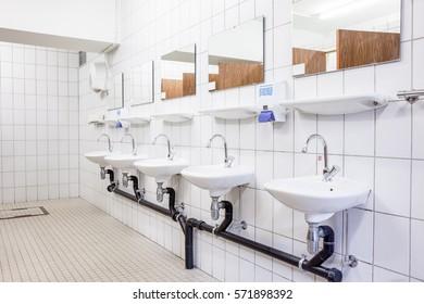 in an public restroom hangs on an wall of an white sink