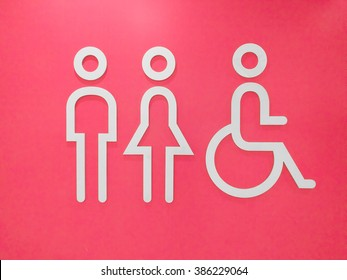 Public restroom signs with a disabled access symbol on pink background.