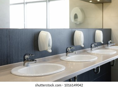 Public restroom with sinks faucets and mirror . Shallow DOF