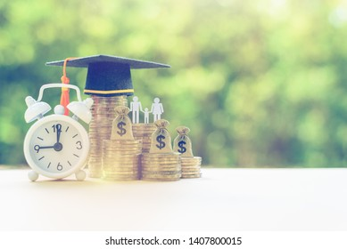Public school funding / education funding, financial concept : Black graduation cap / hat, family members and kid, US dollar bag on rows of rising coins, white clock on a table, green bokeh background