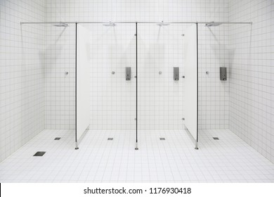 Public shower in spa center. White ceramic tiles on wall and floor.