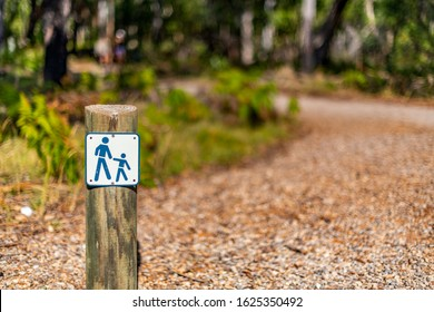 Public signage indicating walking track at Reedy Creek Bush Reserve, central Queensland, Australia. Sign, attached to timber post, has white background with blue adult and child icons.Bokeh background