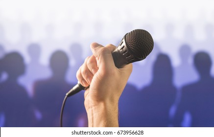 Public speaking and giving speech concept. Hand holding microphone in front of a silhouette audience and crowd of people. Singing to mic in karaoke or talent show concept.