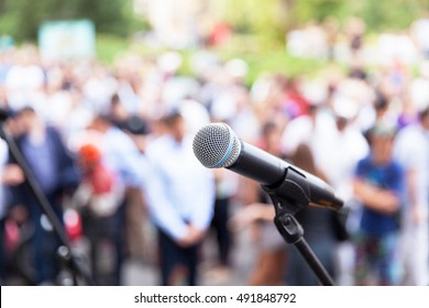 Public speaking. Protest. Microphone in focus against blurred audience.