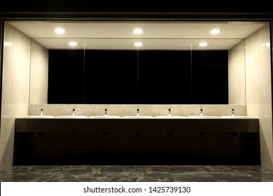 Public toilet and bathroom interior with wash basin.Faucets with of washbasins in public toilet room.Modern sinks with mirror.