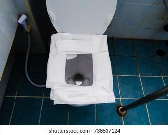 Public toilet : how to use a public restroom concept , Putting the toilet paper on public toilet seat.