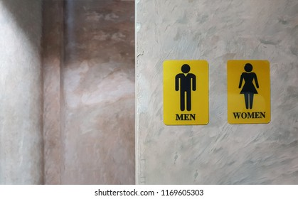 Public toilet of men and women. Sign of lady and gentleman washroom called wc. Mixed gender symbol toilet and restroom behind concrete wall decorate by vintage style in department store. text message
