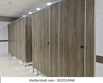 Public toilet, row of toilet, wood partition in public restroom