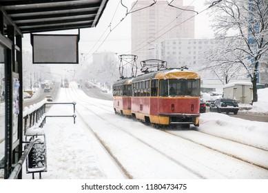 Public tram traffic on winter city street
