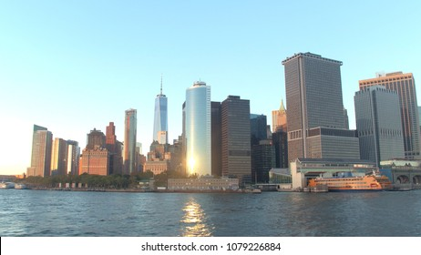 Public transport boat anchored in Staten Island Ferry terminal in Lower Manhattan business district. New York City skyline with contemporary skyscrapers and office buildings at golden light sunset