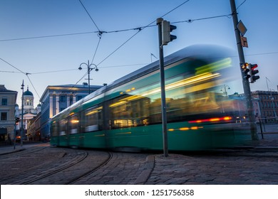 Public transportation in a city. Tram leaving the station, traffic lights, people, street, houses, overhead wires, rails. Movement and lights, long exposure.