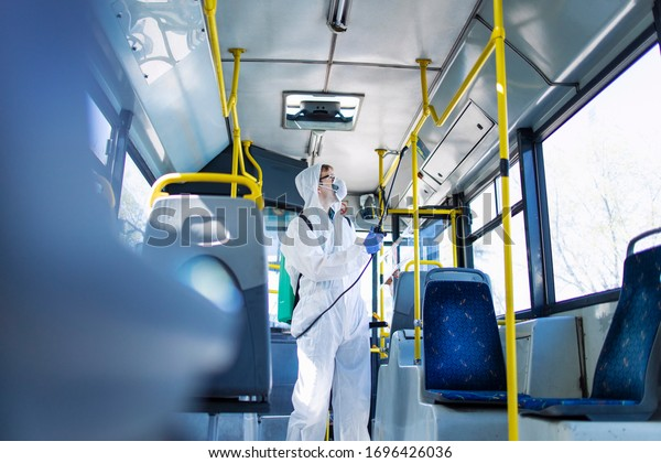 Public transportation healthcare. Man in white protection suit disinfecting and sanitizing handlebars and bus interior to stop spreading highly contagious coronavirus or COVID-19.