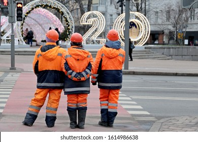 Public utilities workers standing on the city street in front of pedestrian crossing with New Year decorations and the inscription 2020. Janitors in Moscow, street cleaning, concept of unskilled job