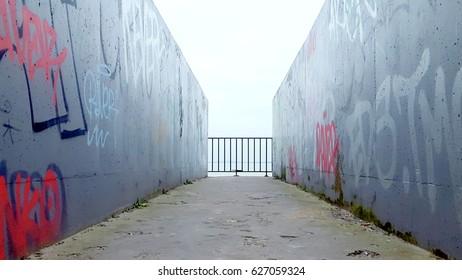 Public walkway access to beach in Blackrock Dublin, Ireland. Grey walls, dramatic perspective, far horizon.