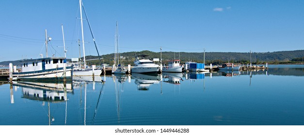 Public waterfront marina/dock with boats in glass smooth tropical water, crystal clear water reflections and blue sky backdrop. Safe port for cruising vessels. Brisbane Water, Gosford, Australia.