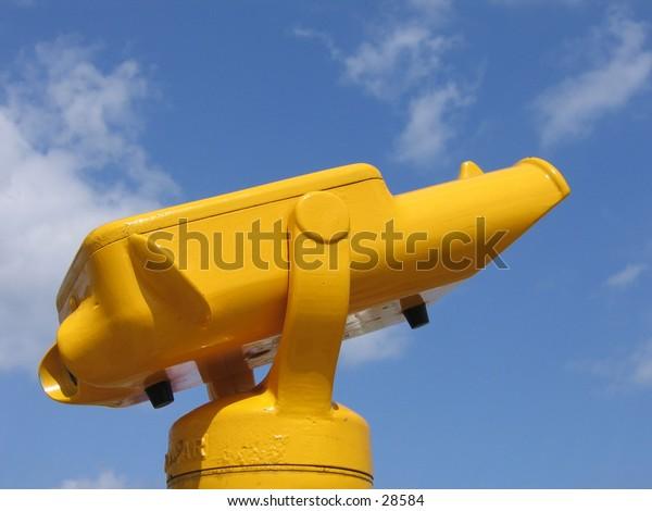 Public yellow binoculars against the blue summer sky.