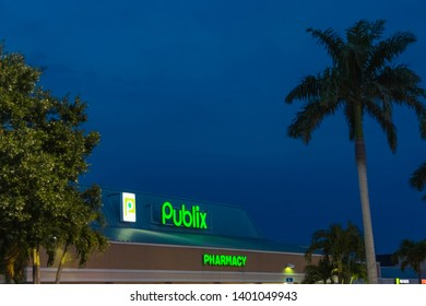 A Publix storefront image taken during twilight hours as seen from the parking lot. The neon signs are lit from the rooftop. The store has palm trees that frame the glass window store entrance.