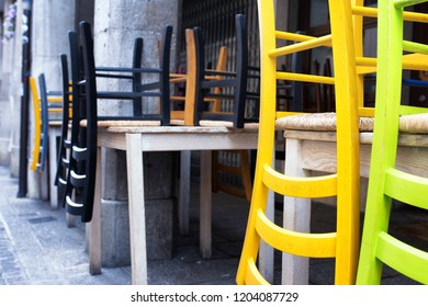 Pub's wooden chairs leaning on tables under an Italian portico. Udine city, Friuli Venezia Giulia region, Italy.